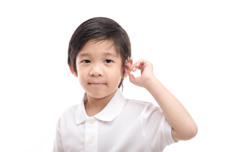 Asian boy touching his ear
